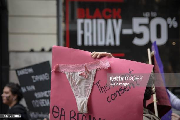 A protester seen holding a placard with a knicker on it during the protest Women demonstrate about the eradication of violence against women