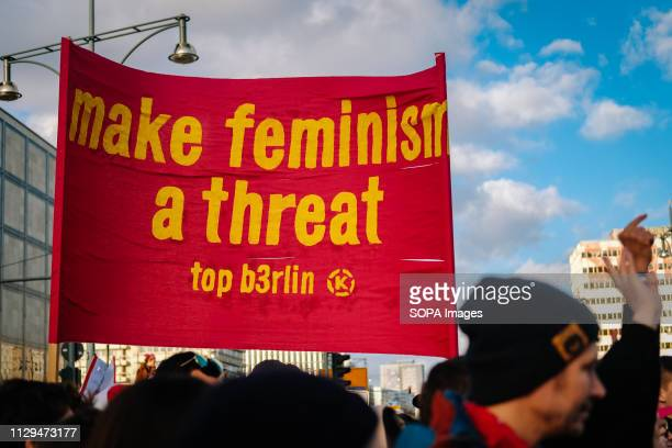 A protester seen holding a placards saying Make feminism a threat during the protest Thousands of people celebrate the international women´s day with...