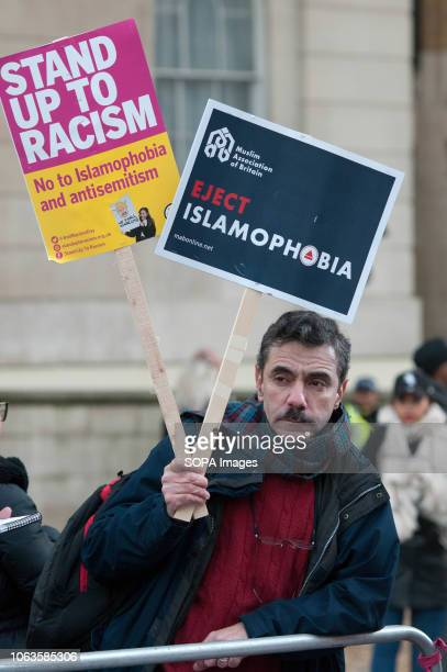 A protester seen holding an antiracist placards during the protest Huge crowds marched from the BBC in Portland Place to Whitehall with flags and...