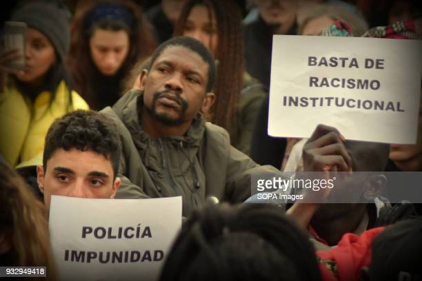A protester seen holding placards during a demonstration in memory of Mame Mbaye Mame Mbaye a Senegalese street vendor who died in Madrid from...