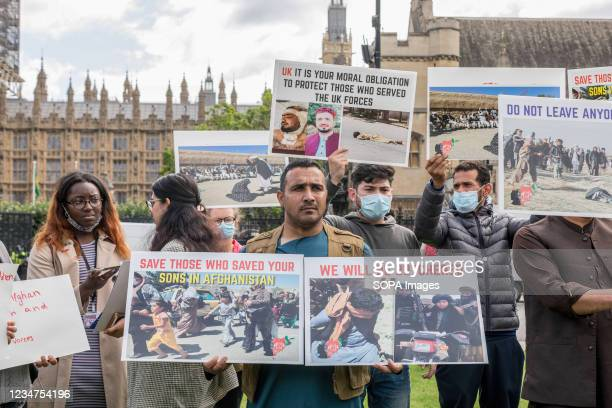 Protester seen holding placards that say 'save those who saved your sons in Afghanistan' and 'we will be butchered' during the demonstration....