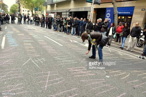 A protester seen painting the road with 177 chalk line for each of the dismissal of the newspaper organization Workers of El Periodico de Cataluña...