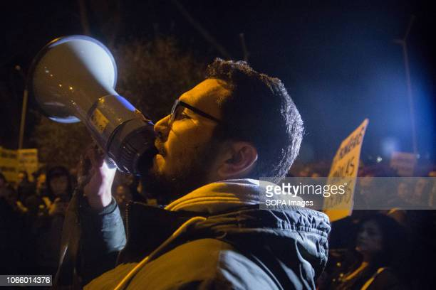 A protester seen shouting for the closure of the Immigration Detention Centers on a megaphone during a protest in front of the Immigration Detention...