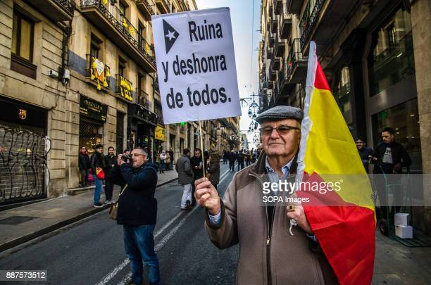A protester seen showing a Spanish flag and a poster with the text Ruin dishonor of all in reference to the economic crisis generated by the...