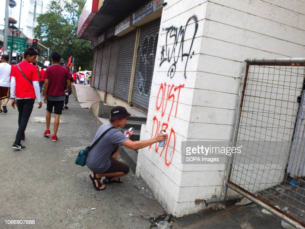 A protester seen spraying paint airing his grievances during the protest Leftist groups stage Bonifacio Day of protest in Mendiola and at the US...