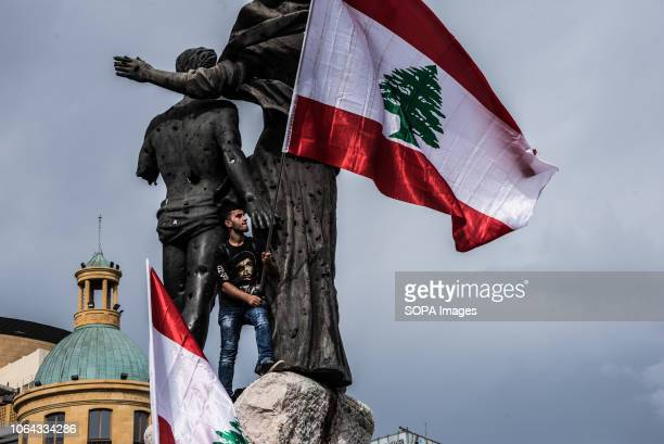 A protester seen standing next to statues while holding a flag during the protest The mood was generally deflated as a handful of protesters almost...