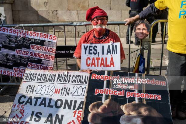 A protester seen surrounded by several placards and posters during a demonstration to support Carles Puigdemont former Catalan President in front of...