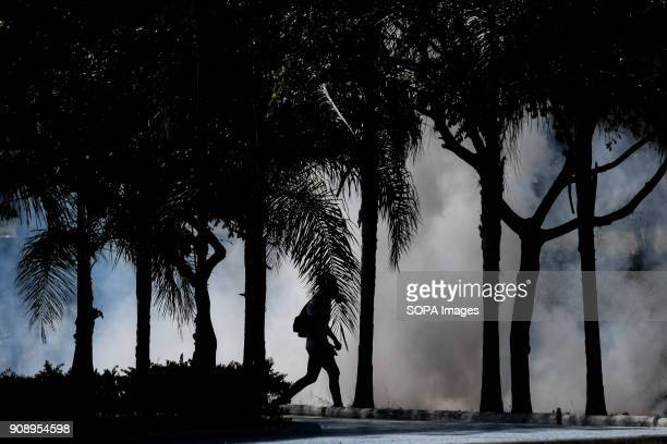 A protester seen taking cover behind a tree as police fired multiple tear gas to the protesters Demonstrators clashed with security forces during a...