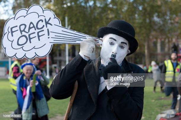 Protester seen wearing makeup to looks like Charles Chaplin while holding a placard during the protest The newly formed Extinction Rebellion group...