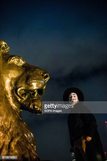 A protester seen wearing the Guy Fawkes mask at Trafalgar square Demonstrators attend the Annual Million Mask March bonfire night protest advertised...