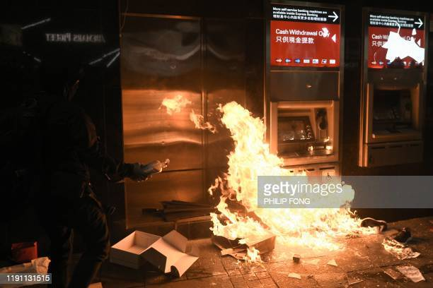 Protester sets fire to an ATM outside an HSBC branch in Central following a pro-democracy march in Hong Kong on January 1, 2020. - Tens of thousands...