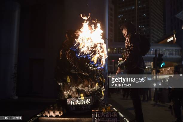Protester sets fire to an HSBC lion statue outside the bank's headquarters in Central following a pro-democracy march in Hong Kong on January 1,...