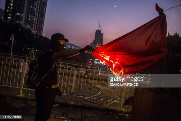 TOPSHOT A protester sets fire to the Chinese national flag in the Sha Tin district of Hong Kong on October 1 as violent demonstrations take place in...