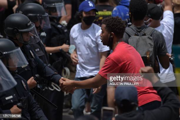 Protester shakes hands with an LAPD officer during a demonstration over the death of George Floyd in Hollywood, California on June 2, 2020. -...