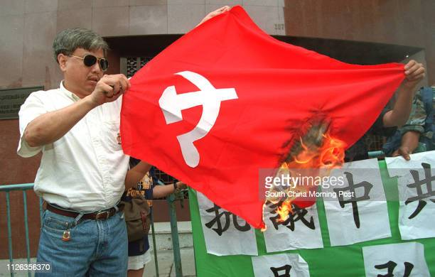 Protester Shing Wai Pong from the Chinese Liberal Democratic Party burns the flag of Chinese Communist Party in front of the Xinhua News Agency where...