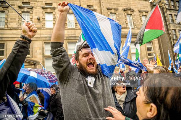 Protester shouting slogans holds a Saltire during the Pro-Unionist counter-protest. Thousands of Scottish independence supporters marched through...