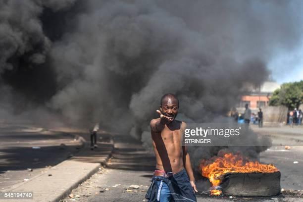 TOPSHOT A protester shouts antiMugabe slogans in front of burning tyres during a demonstration on July 6 2016 in Makokoba Bulawayo Zimbabwe Residents...