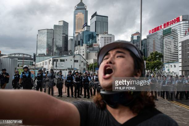 TOPSHOT A protester shouts in front of police outside the government headquarters after the annual flag raising ceremony to mark the 22nd anniversary...