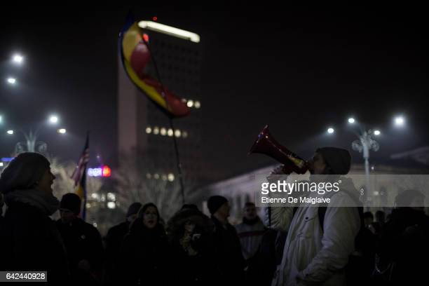 A protester shouts slogan trough a bull horn while hundreds gather every evening in front of the government headquarters at the Victory square and...