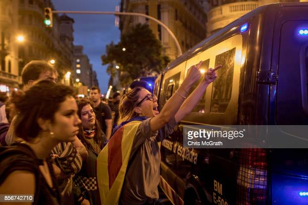 A protester shouts slogans and gesture toward the General Direction of the National Police of Spain building in protest against the violence that...