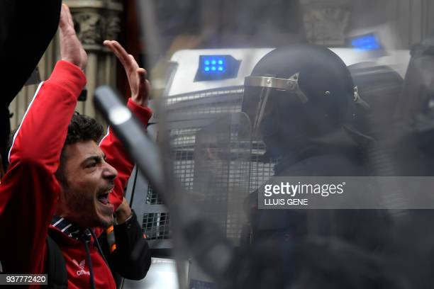 A protester shouts slogans as riot police block the road leading to the central government offices during a demonstration in Barcelona on March 25...