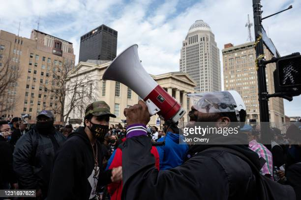 Protester shouts through a megaphone as other demonstrators gather during a Breonna Taylor memorial march near Jefferson Square Park on March 13,...
