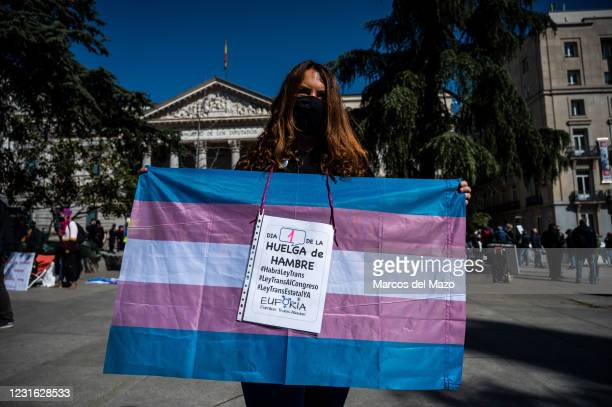 Protester showing a trans pride flag in front of the Congress of Deputies as a group start a hunger strike demanding a National Law for Transgender...