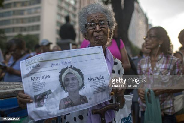 A protester shows a local newspaper during a demonstration against the murder of Brazilian councilwoman and activist Marielle Franco in front of...