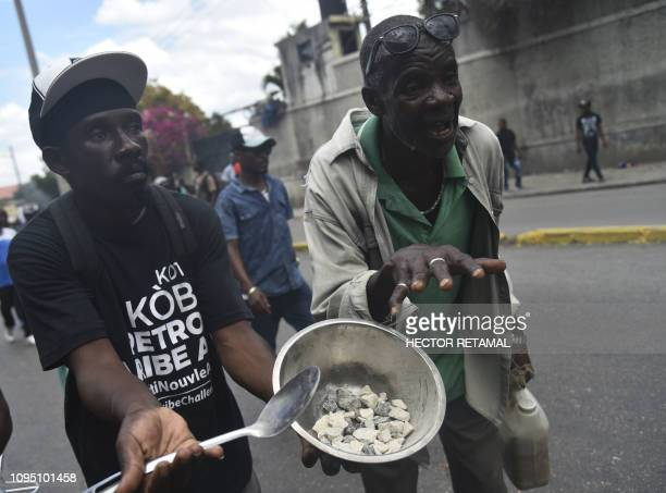 TOPSHOT A protester shows a plate with stones used to protest against the high price of food and consumer goods in Haiti during a march through the...