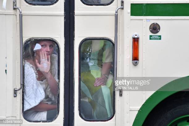 Protester shows her glued palm against a window, as police officers surround a vehicle parked across the road by climate activists from the...