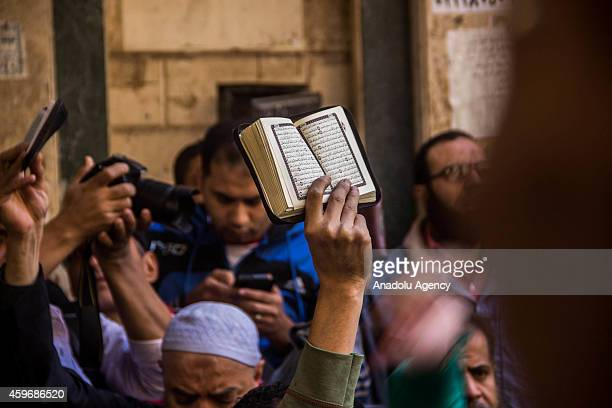 A protester shows Islam's holy book Quran during an antiregime rally following the Friday Prayer in ElMatareya neighborhood of Cairo Egypt on...