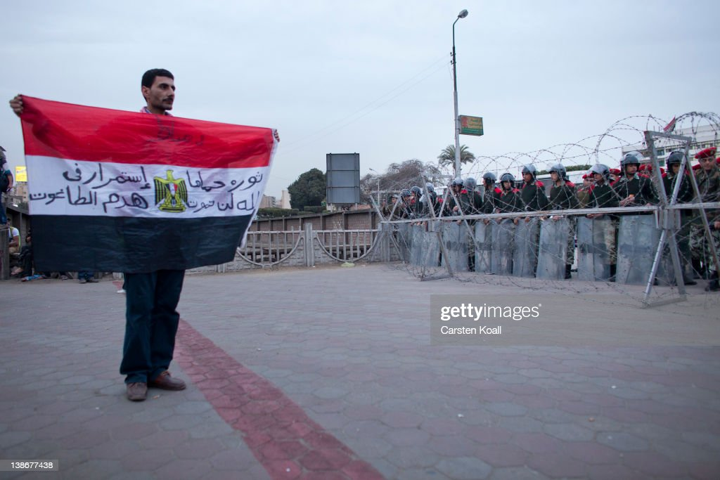 A protester shows the Egyptian national flag to soldiers staying behind a barbed wire barrier by the army forces to stop protesters after a demonstration against the military rulers of the country on February 10, 2012 in Cairo, Egypt. Egyptian people await the upcoming first anniversary of the resignation of the former Muhammad Hosni Mubarak after his 30-year term on 11 February last year. The poor economic condition of the country and the unrest in the past are a threat to the transition to a democracy.