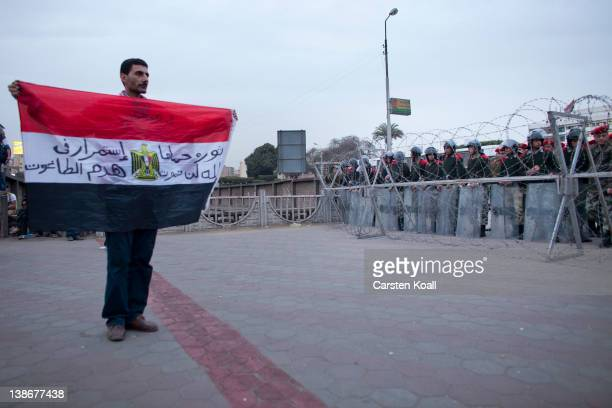 A protester shows the Egyptian national flag to soldiers staying behind a barbed wire barrier by the army forces to stop protesters after a...