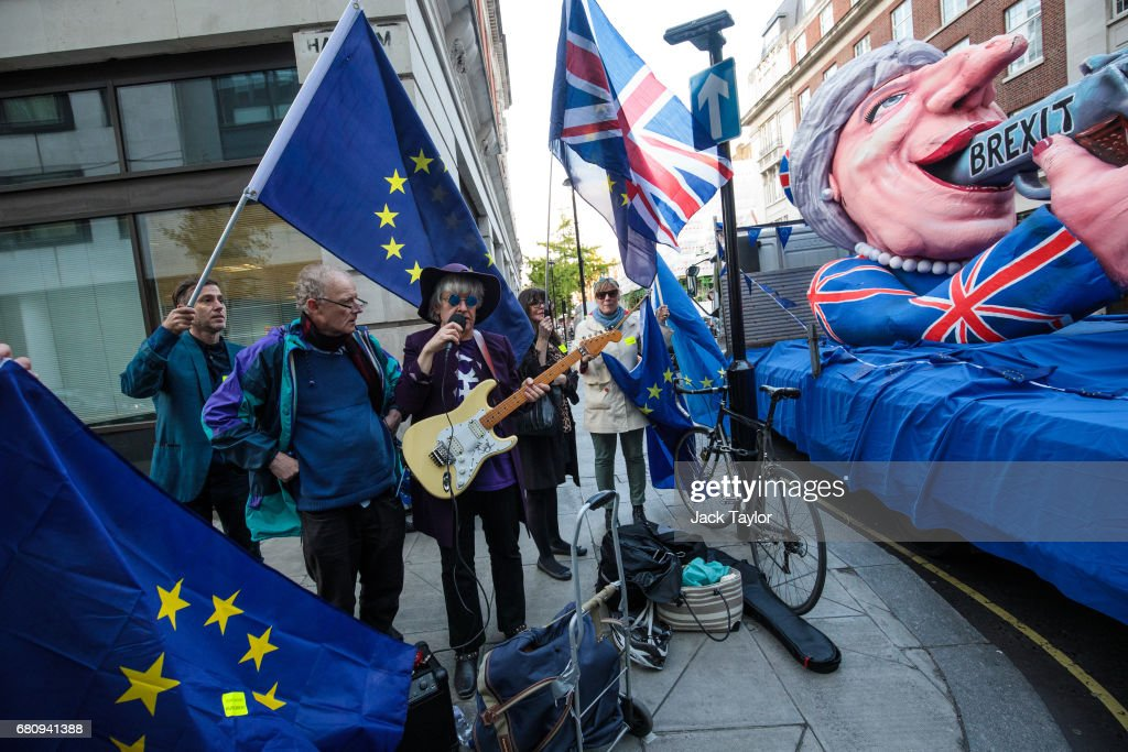 A protester sings and plays guitar beside an effigy of British Prime Minister Theresa May with a gun during a demonstration outside BBC's Broadcasting House as Mrs May and her husband Philip May give a joint interview on the One Show on May 9, 2017 in London, England. Campaigning is underway ahead of the June 8th general election.