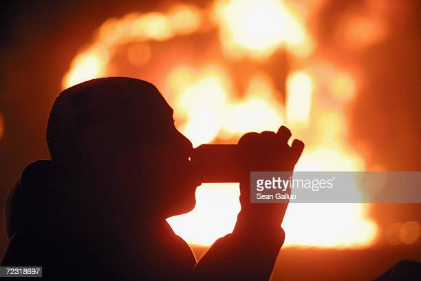 A protester sips a beer in front of a burning car during May Day riots May 1 2003 in the Kreuzberg district of Berlin Germany An estimated one...