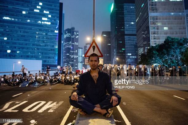 TOPSHOT A protester sits at the middle of Harcourt Road in Hong Kong after a protest against a controversial extradition law proposal in Hong Kong on...