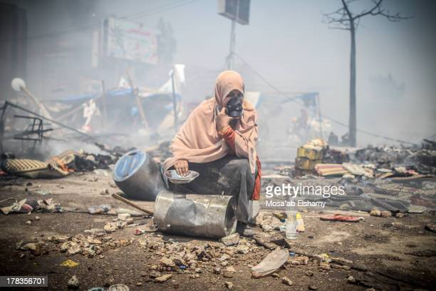 CONTENT] A protester sits holding cooking pots sits amid the rubble during the clearing of one of the two sitins of ousted president Morsi supporters...