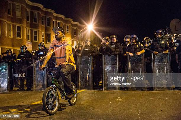 Protester sits in front of riot police minutes before a mandatory, city-wide curfew of 10 p.m. Near the CVS pharmacy that was set on fire yesterday...