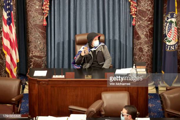 Protester sits in the Senate Chamber on January 06, 2021 in Washington, DC. Congress held a joint session today to ratify President-elect Joe Biden's...