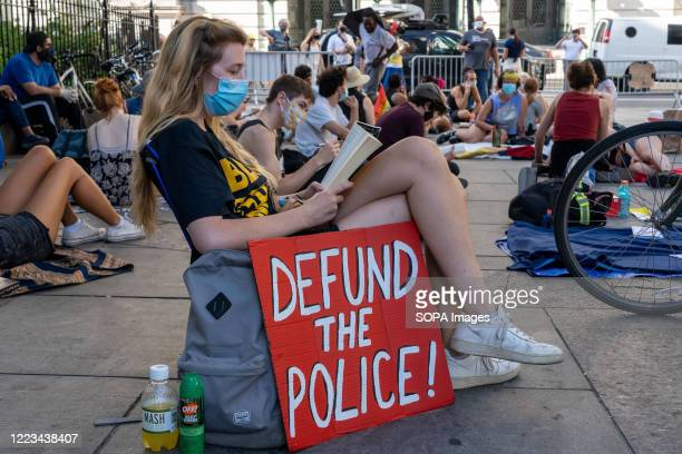 Protester sits near a placard that says Defund the police as the Black Lives Matter and other activists camp in a park outside the City Hall during...