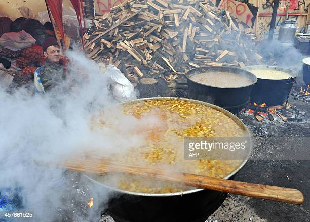A protester sits next to giant cooking pots at the camp of the Ukrainian opposition on Independence Square in Kiev on December 19 2013 Yanukovych...