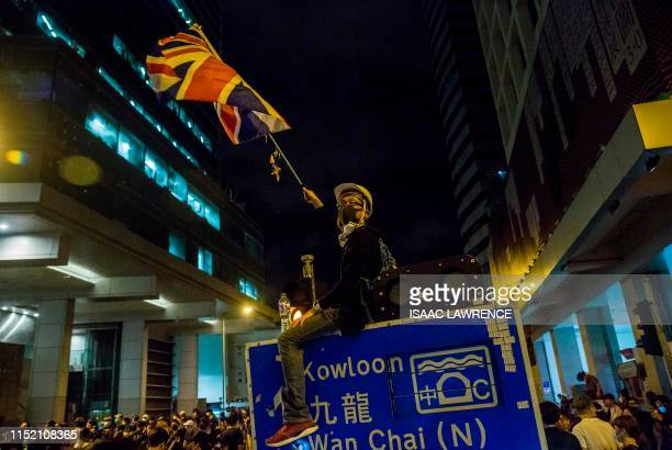 TOPSHOT A protester sits on a street sign waving a Union Jack flag at the police headquarters in Hong Kong early on June 27 2019 Hong Kong protesters...