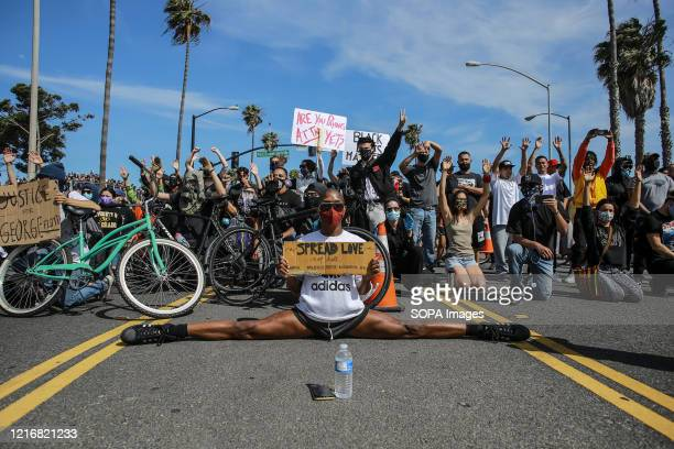 A protester sits with his legs completely spread on the ground while holding a sign that reads Spread Love Not Hate during a protest against the...