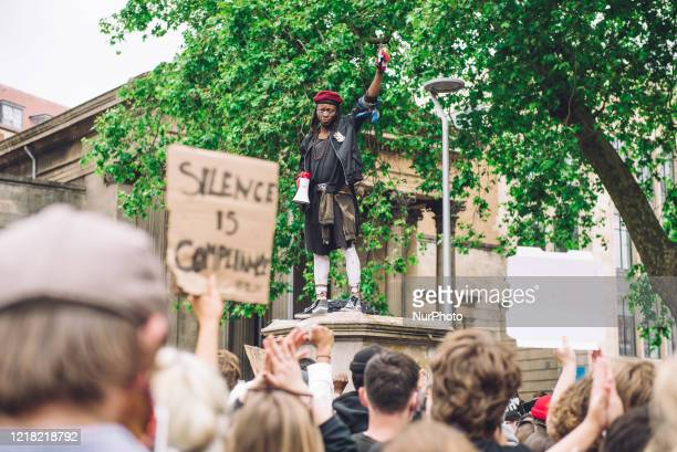 Protester speaks to a crowd from the pedestal that once hosted the statue of Edward Colston, a slave trader who lived in the 17th century and played...