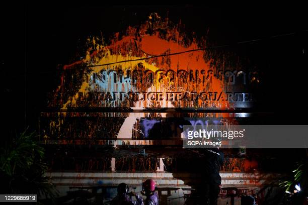 Protester spraying colours on the royal Thai police headquarter label during the demonstration. Thousands of pro-democracy protesters gathered at...