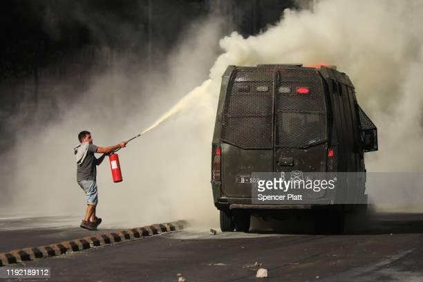 A protester sprays fire extinguishing powder to riot police truck in downtown Santiago as demonstrations continue against Chilean President Sebastian...