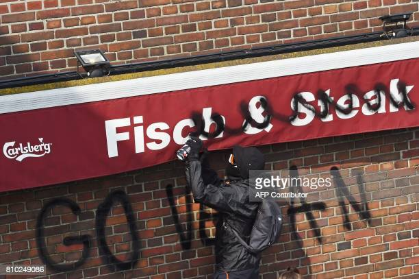 A protester sprays 'Go Vegan' on a fish and steak shop on July 7 2017 in Hamburg northern Germany where leaders of the world's top economies gather...