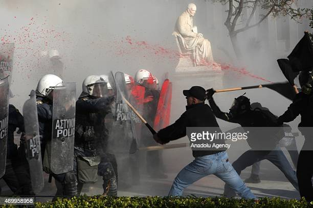 Protester sprays red paint at police as other attack with sticks during a rally in front of the Athens University, which is under occupation by...