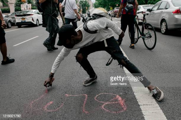 Protester sprays red paint onto the street during a march against police brutality on June 11, 2020 in New York City. Demonstrations against systemic...
