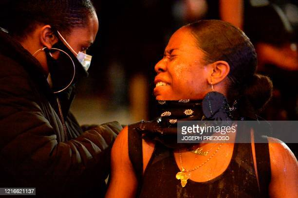 A protester squints after being sprayed with pepper spray during clashes with police after a demonstration over the death of George Floyd an unarmed...